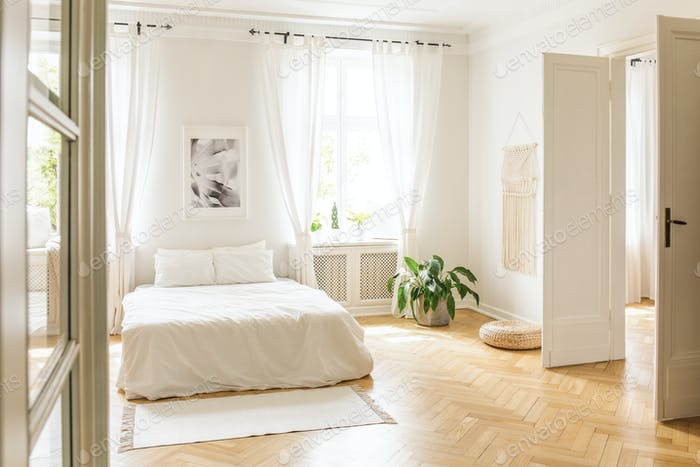 Poster above white bed with pillows in bright bedroom interior w