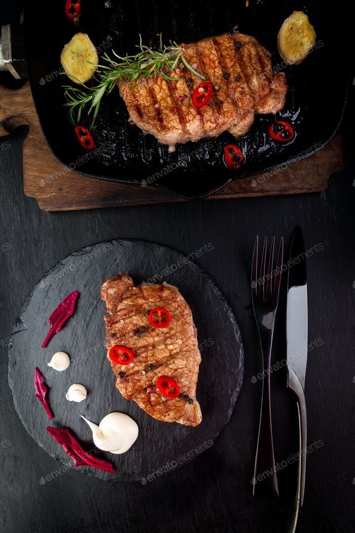 Grilled pork steak on slate plate.