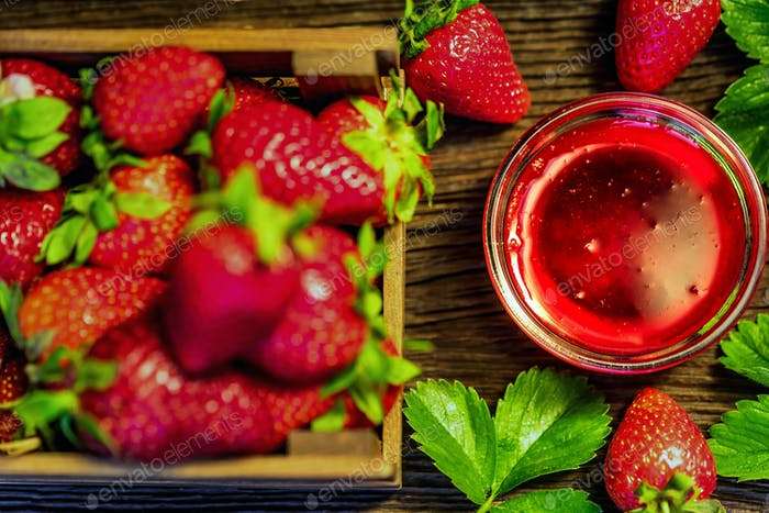 Fresh strawberries in wooden box and liqueur close
