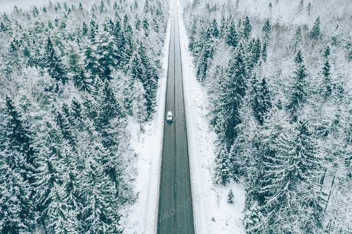 Aerial view of winter road with car and snow covered trees in the forest