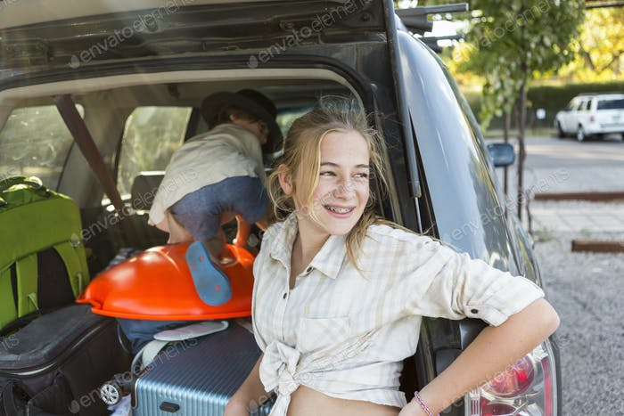 13 year old girl in back of SUV with luggage