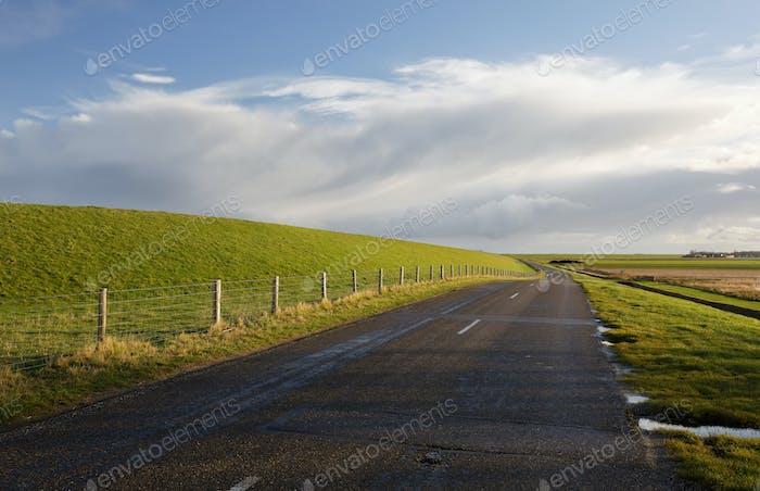 Straße zwischen grünen Hügeln und blauem Himmel