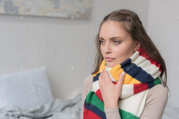 Kranke Frau in einem Schal über Hals sitzt in einem Schlafzimmer
