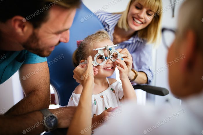 Ophthalmologist is checking the eye vision of little cute girl in modern clinic