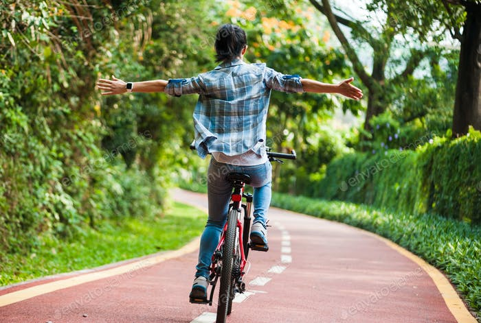 Woman riding mountain bike with her arms outstretched