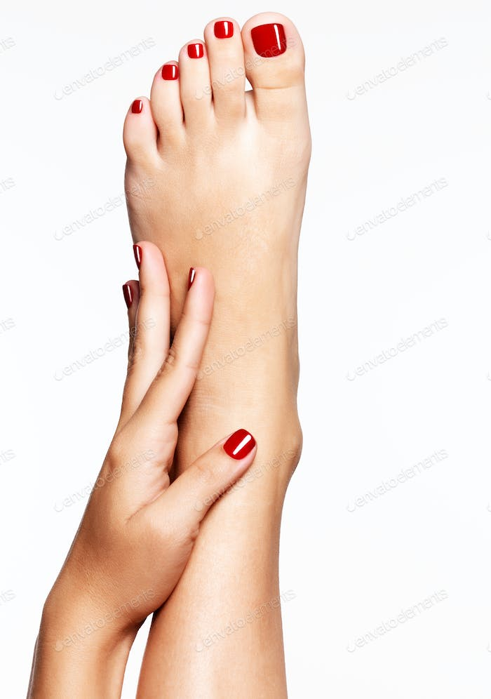 Closeup photo of a female feet with beautiful red pedicure