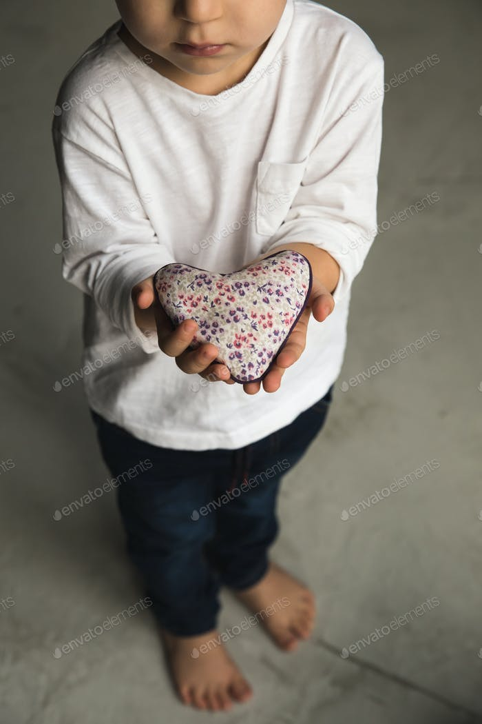 Baby boy hands giving toy heart.