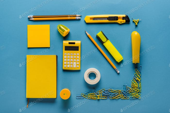 composition of yellow school supplies on blue
