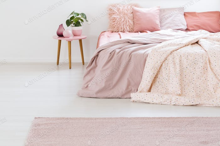 Plant on table next to bed with pink sheets and cushions in past
