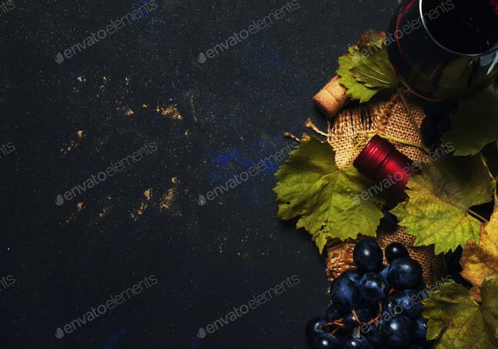Red wine in glass, vine and grapes, black background, top view