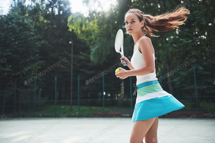 Woman in sportswear serves tennis ball