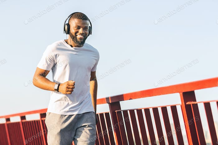 Smiling african guy running along the bridge