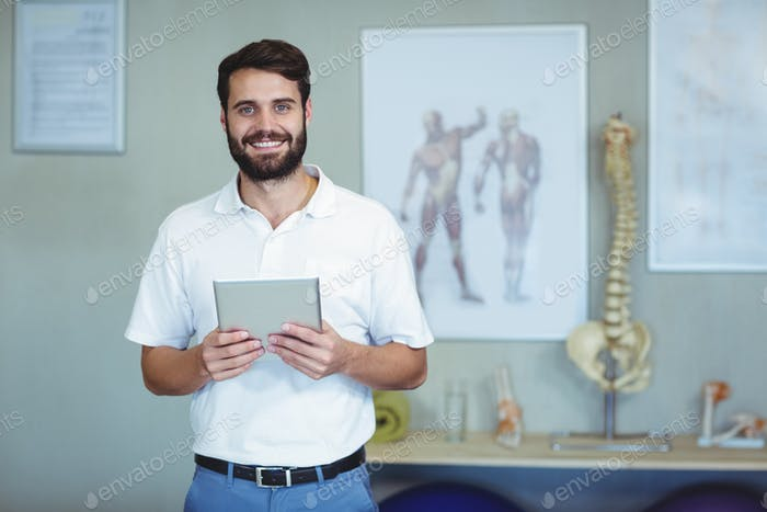 Portrait of physiotherapist holding a digital tablet
