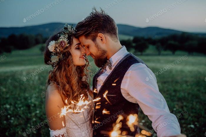 Hermosa novia y novio con bengalas en un prado.