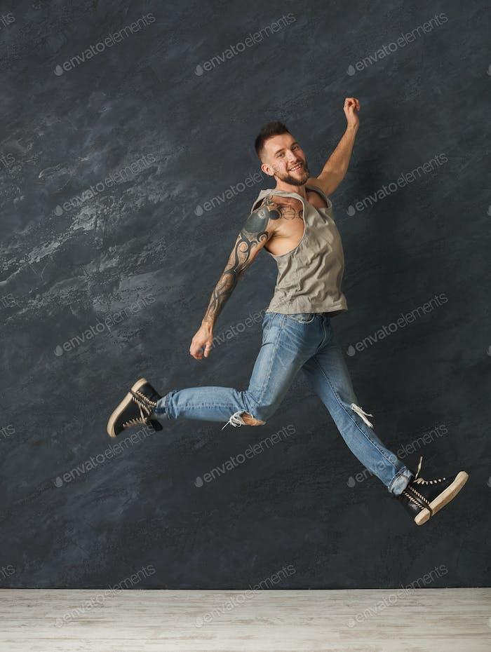 Happy handsome man jumping in studio