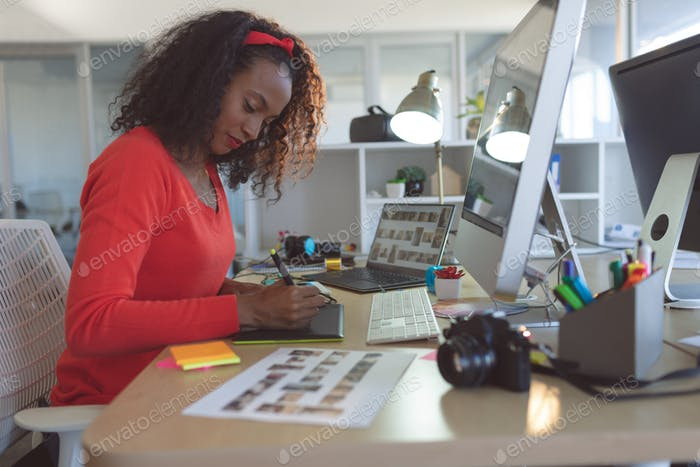 Female graphic designer using graphic tablet at desk in a modern office