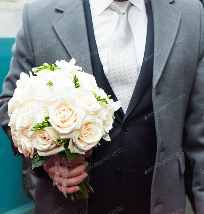 bouquet of white flowers in male hands