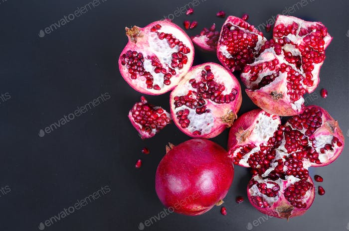 Ripe juice pomegranate fruit on black background - whole and cut, top view