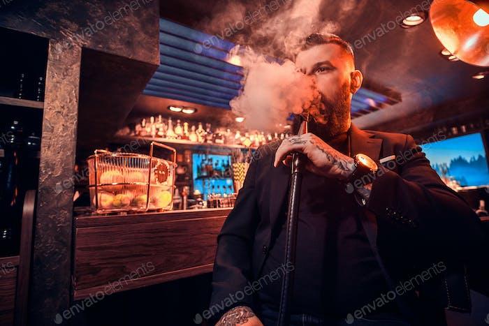 Porträt tätowierter bärtiger Mann, der die Wasserpfeife raucht, macht schönen Dampf
