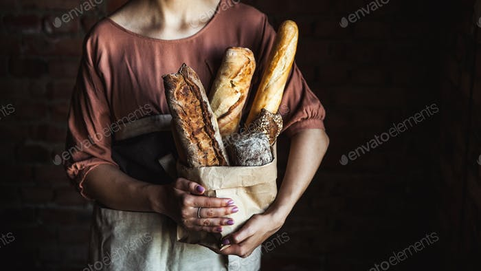 French baguettes in female hands on a black background. homemade baking
