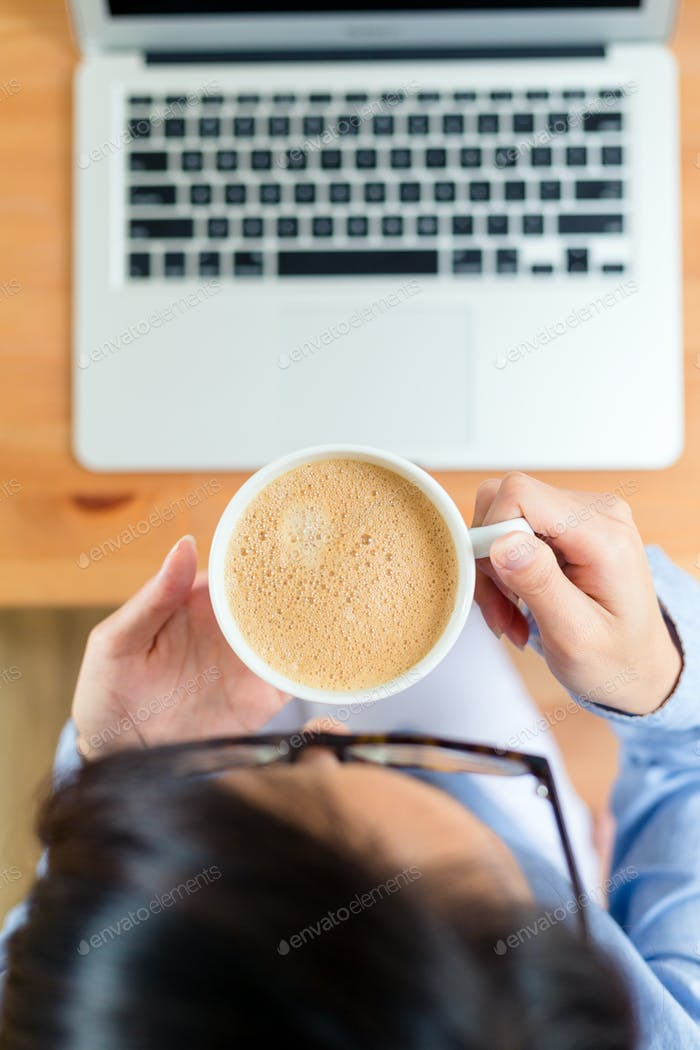 Top view of woman drink of coffee with her laptop computer