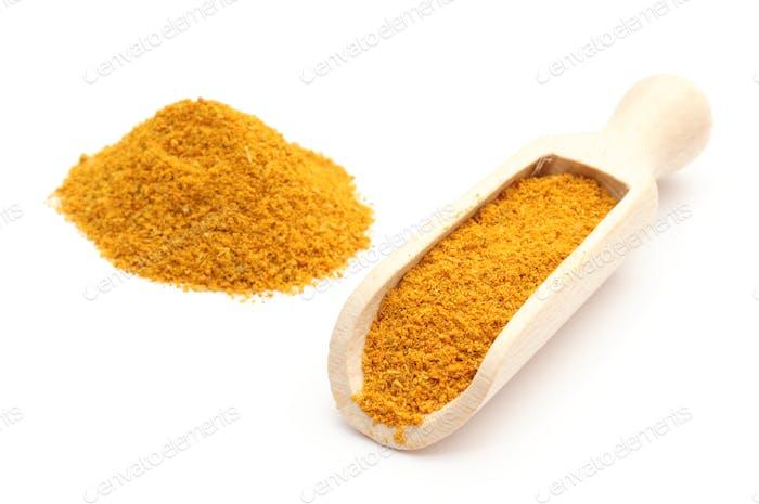 Orangencurry auf Holzlöffel. Isoliert auf weißem Hintergrund