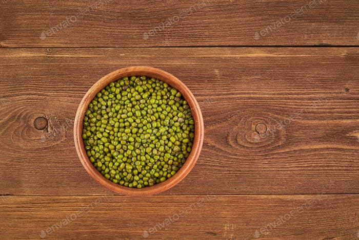 Mung beans in wooden bowl on brown background, top view, copy space
