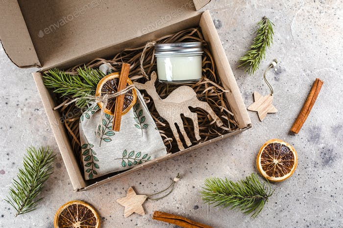 Christmas gift box with hugge items textile pouch, candle, wooden toy for tree. Care package concept