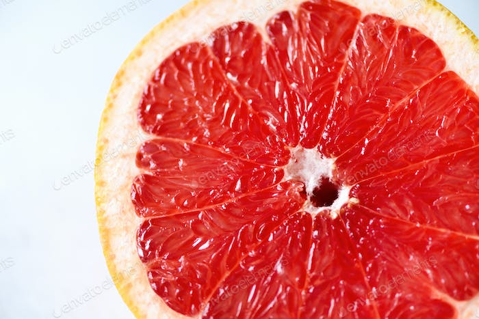 Grapefruit sliced half on grey background. Citrus fruit macro. Copy space, top view
