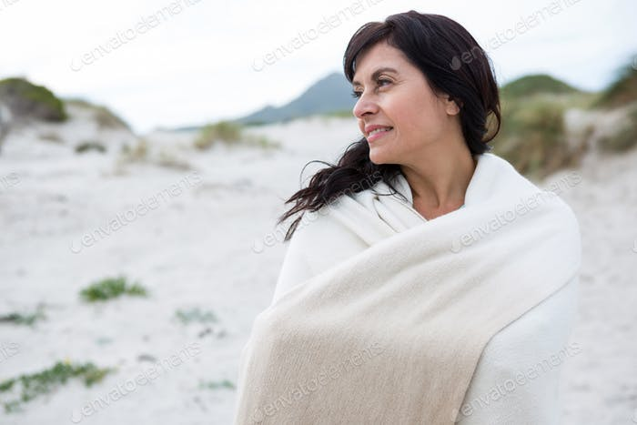 Thoughtful woman wrapped in shawl on beach