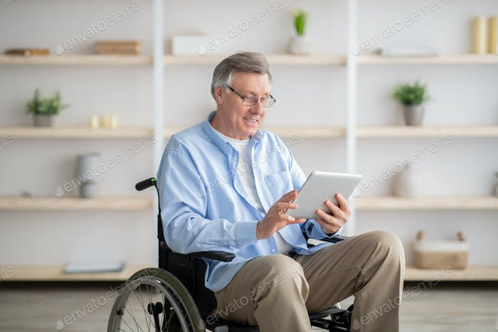 Joyful impaired senior man in wheelchair using tablet computer at home