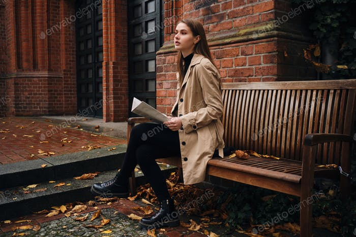 Beautiful girl confidently looking away reading newspaper on bench outdoor