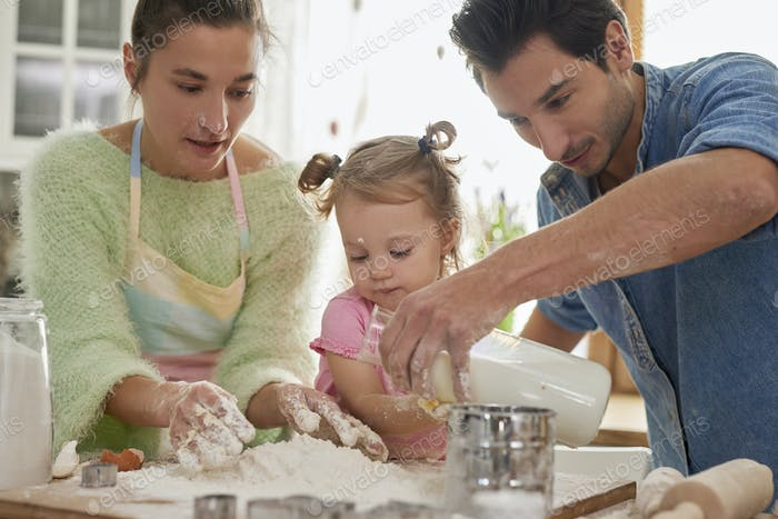 Little girl making cookies with parents