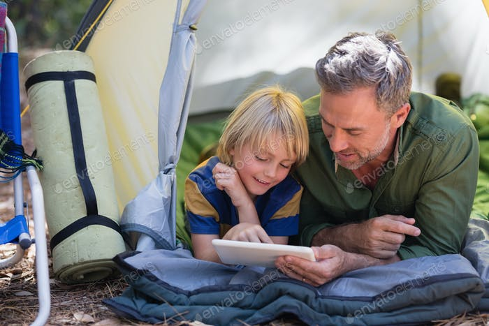 Father and son using digital tablet while resting at campsite