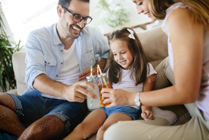 Happy family drinking juice together in their house