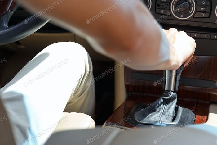 driver's right hand shifting the gear stick in car, close up image