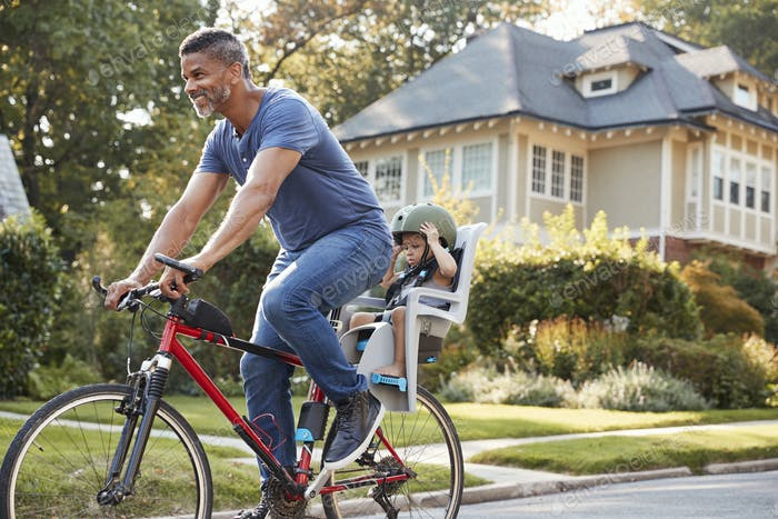 Father Cycling Along Street With Daughter In Child Seat