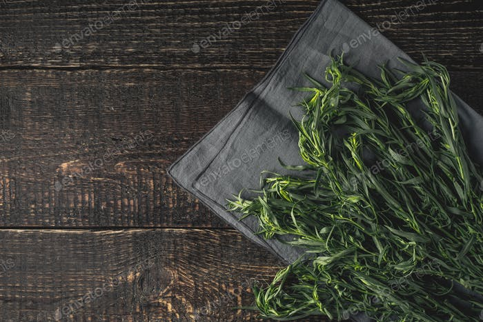 Tarragon on the grey napkin on the wooden table top view