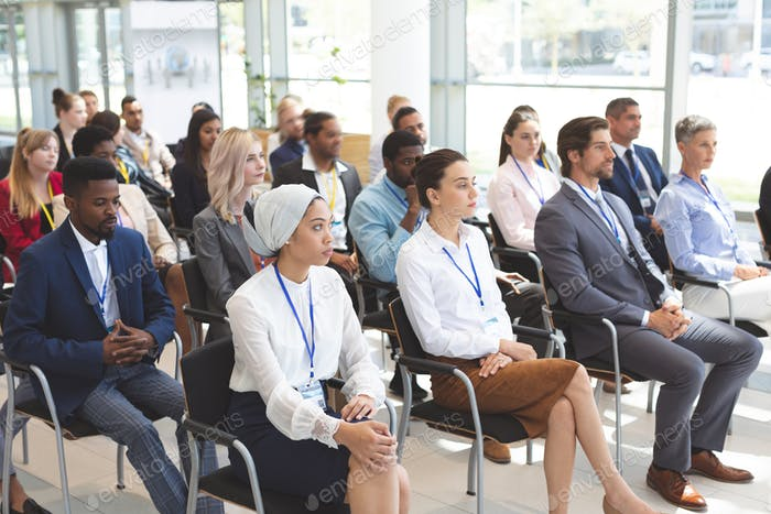 Side view of group of diverse business people attending a business seminar in office building