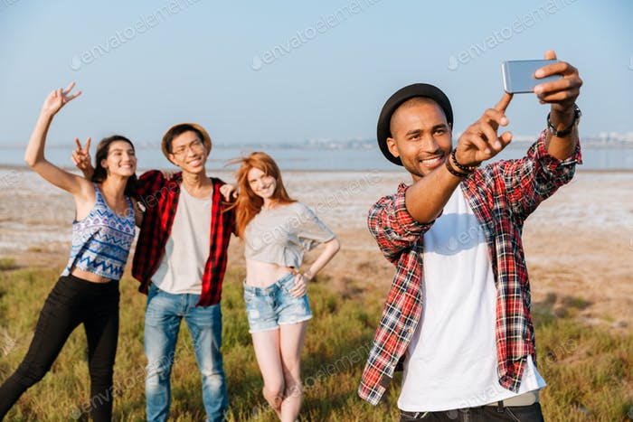 Happy man standing and taking selfie with his friends outdoors