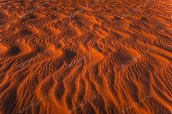 Increíble vista de la Textura de las dunas de Arena onduladas iluminada por la luz del sol del atardecer