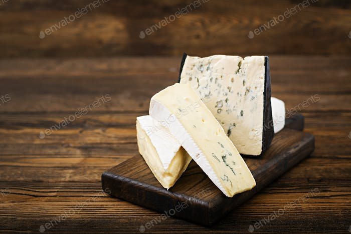 Assortment of cheeses. Camembert, dor blu, brie on a wooden background
