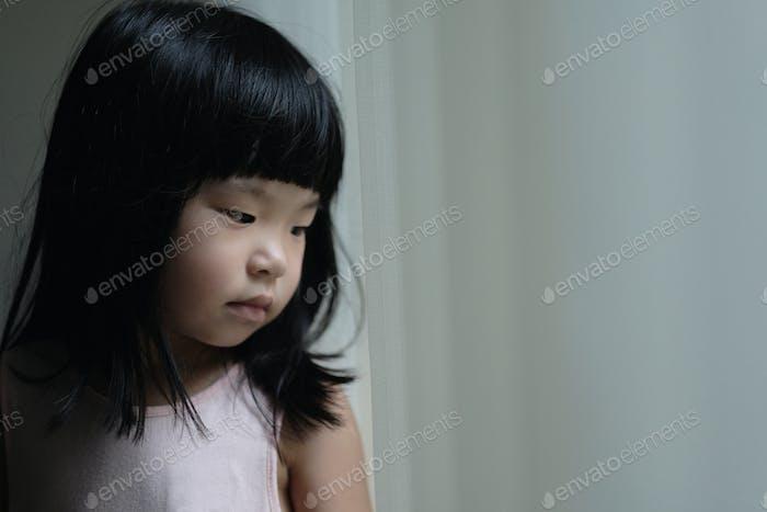 Sad lonely little girl standing beside a window