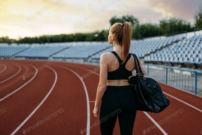 Female runner holds sport bag, training on stadium