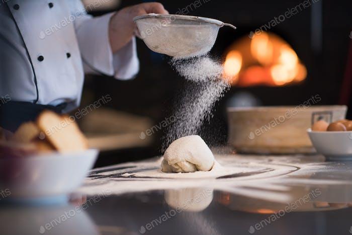 chef sprinkling flour over fresh pizza dough