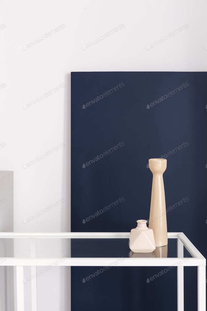 Two light pink vases on the glass shelf, white and dark blue bac