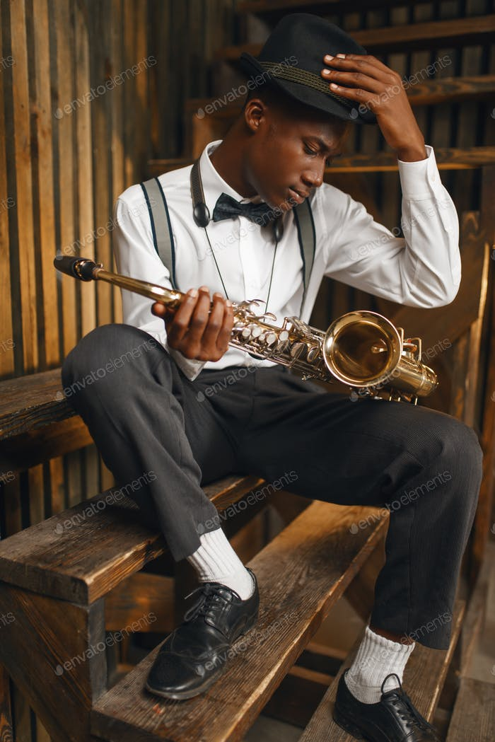 Black jazz musician sitting with saxophone