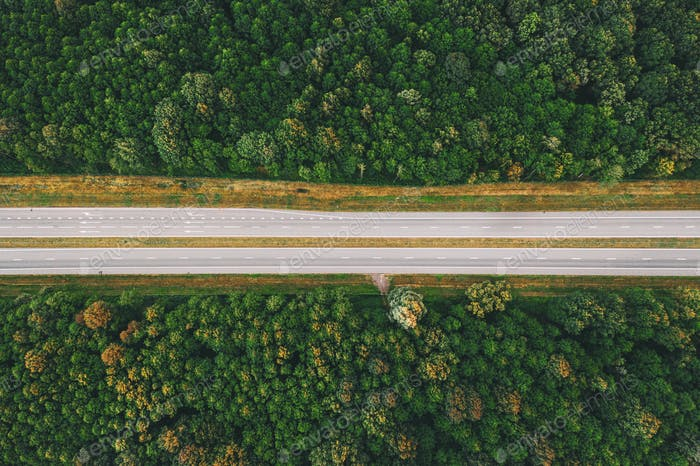 Aerial View Of Highway Road Through Green Forest Landscape In Summer.