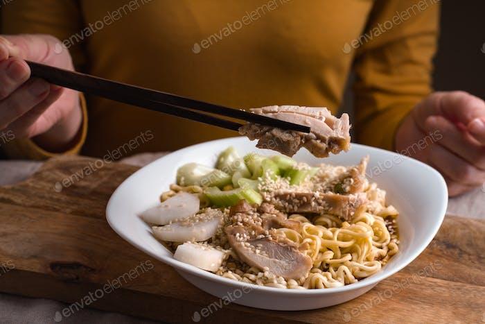 Woman eating chopsticks chicken and ramen noodles