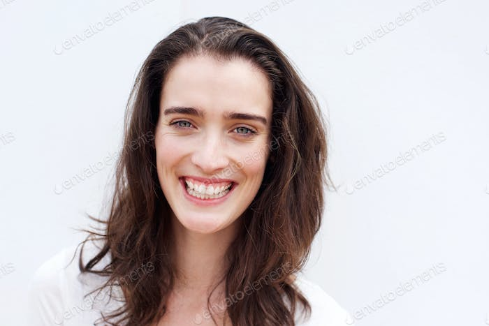 Cheerful young woman smiling against white background